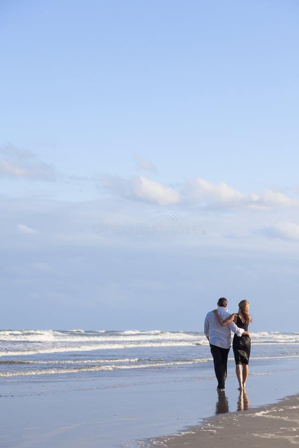 Pares románticos del hombre y de la mujer que recorren en una playa imagen de archivo