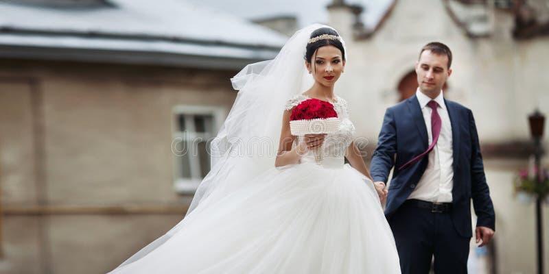 Pares románticos del recién casado que llevan a cabo las manos y que presentan en europea viejo fotos de archivo