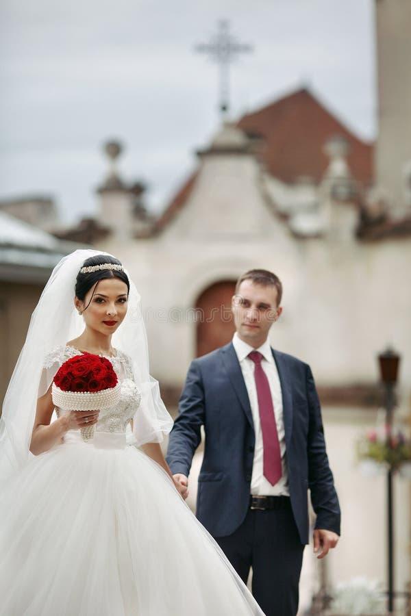 Pares románticos del recién casado que llevan a cabo las manos y que presentan en europea viejo foto de archivo libre de regalías