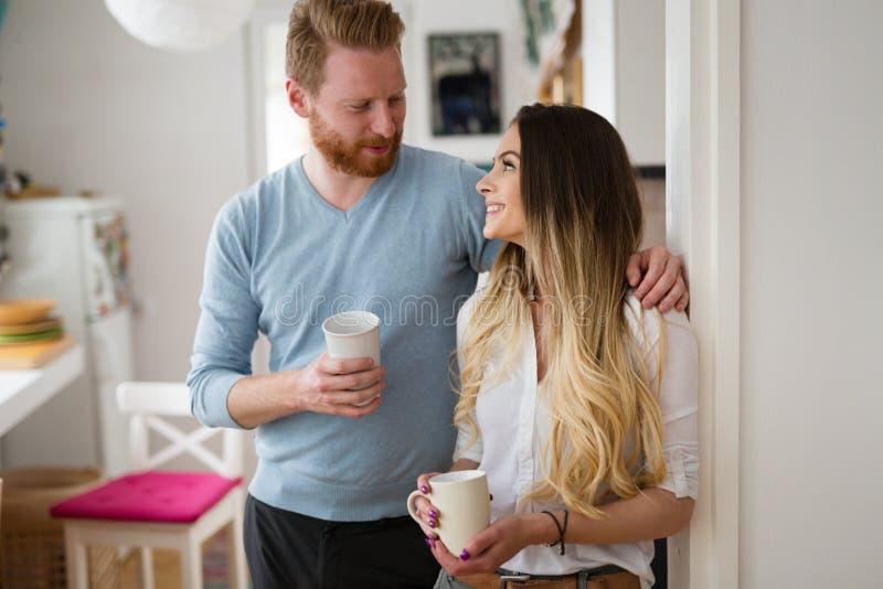 Pares románticos en el amor en casa que bebe el café y la sonrisa foto de archivo