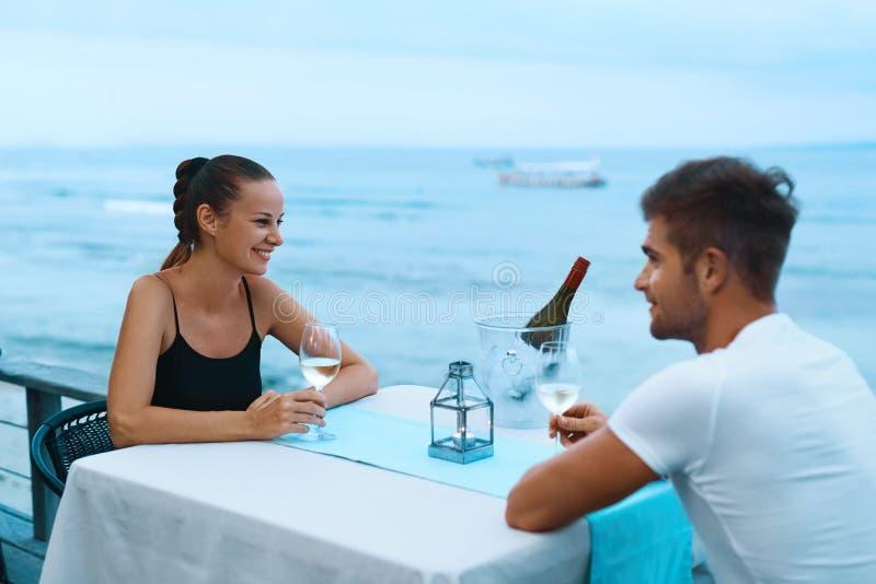 Pares románticos en el amor que cena en el restaurante de la playa del mar fotos de archivo
