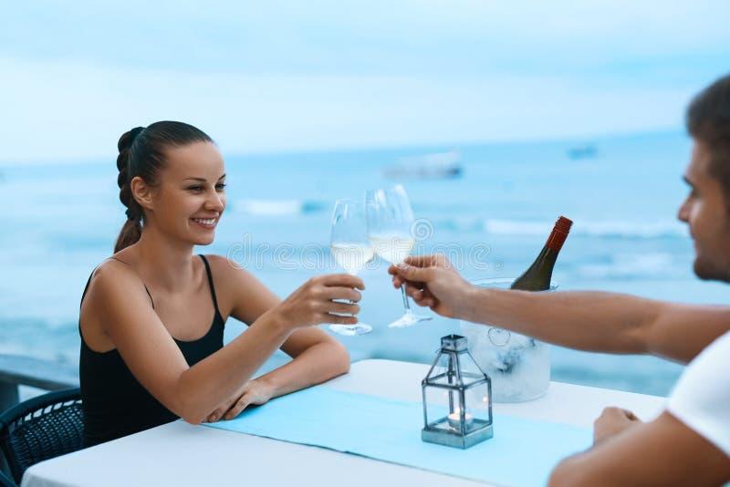 Pares románticos en el amor que cena en el restaurante de la playa del mar fotografía de archivo