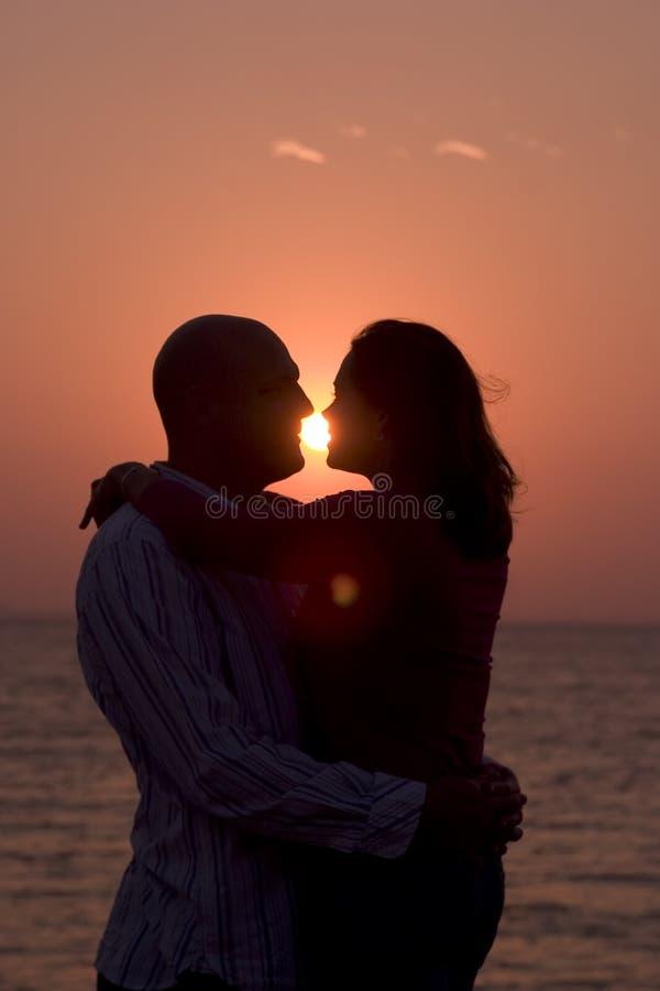 Pares románticos en la puesta del sol fotos de archivo
