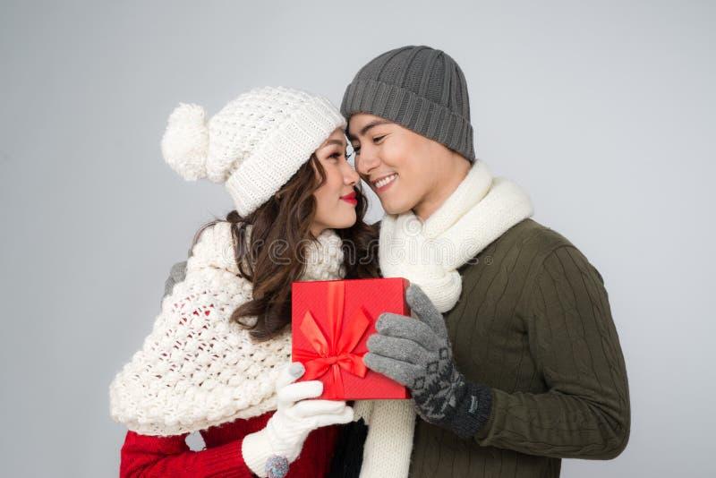 Pares románticos en suéteres con la caja de regalo roja imágenes de archivo libres de regalías
