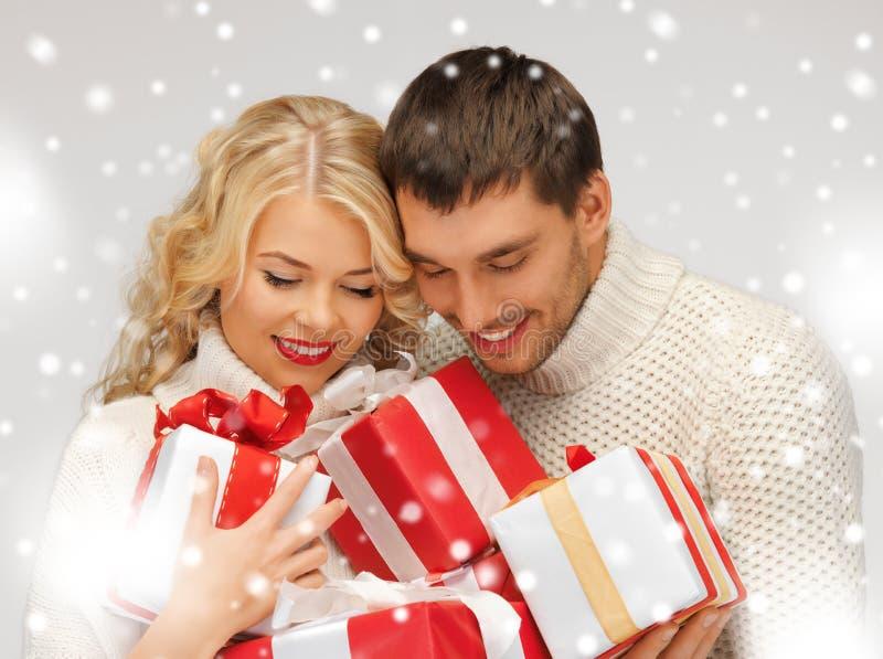 Pares románticos en suéteres con las cajas de regalo fotos de archivo