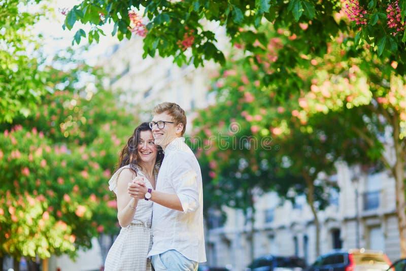 Pares románticos felices en París, abrazando debajo de las castañas rosadas en la plena floración imagen de archivo libre de regalías