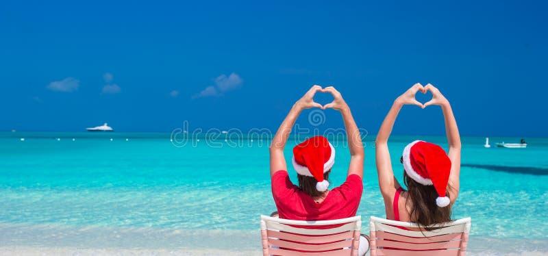 Pares románticos felices en Santa Hats roja en la playa fotos de archivo