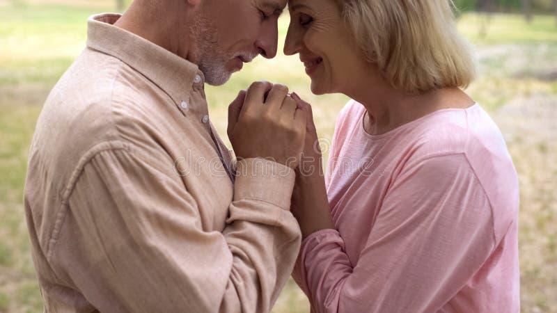 Pares románticos felices que llevan a cabo las manos, abuelos sonrientes en el amor, proximidad imágenes de archivo libres de regalías