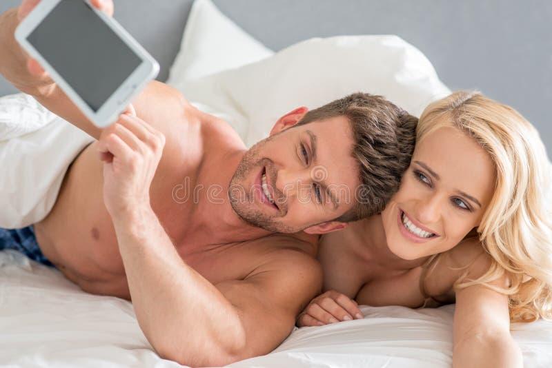 Pares románticos felices que toman imágenes usando el teléfono fotografía de archivo libre de regalías