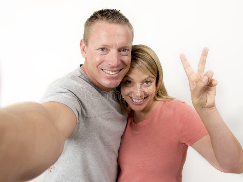 Pares románticos felices y atractivos hermosos jovenes con el marido y esposa o novia y novio que toman el autorretrato del selfi foto de archivo