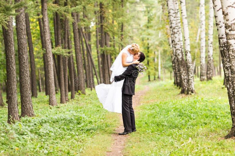 Pares románticos hermosos de la boda que se besan y que abrazan al aire libre imagen de archivo