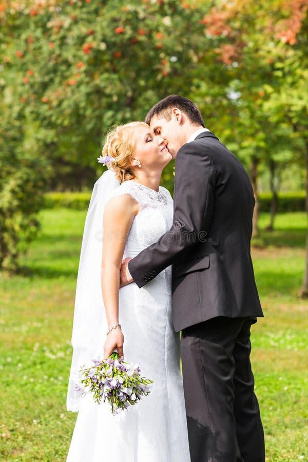 Pares románticos hermosos de la boda que se besan y que abrazan al aire libre foto de archivo libre de regalías