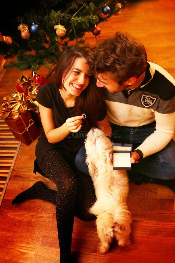 Pares románticos jovenes debajo del árbol de navidad en casa con los regalos de Navidad imagenes de archivo