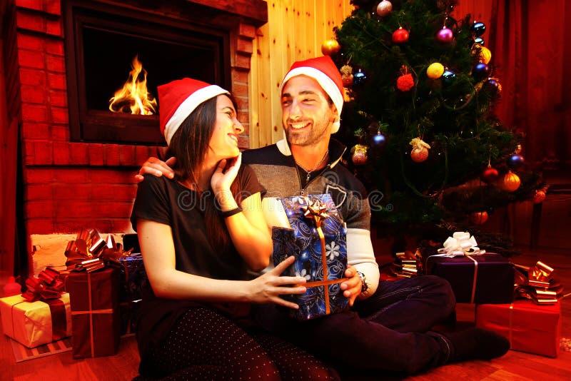 Pares románticos jovenes debajo del árbol de navidad en casa con los regalos de Navidad foto de archivo