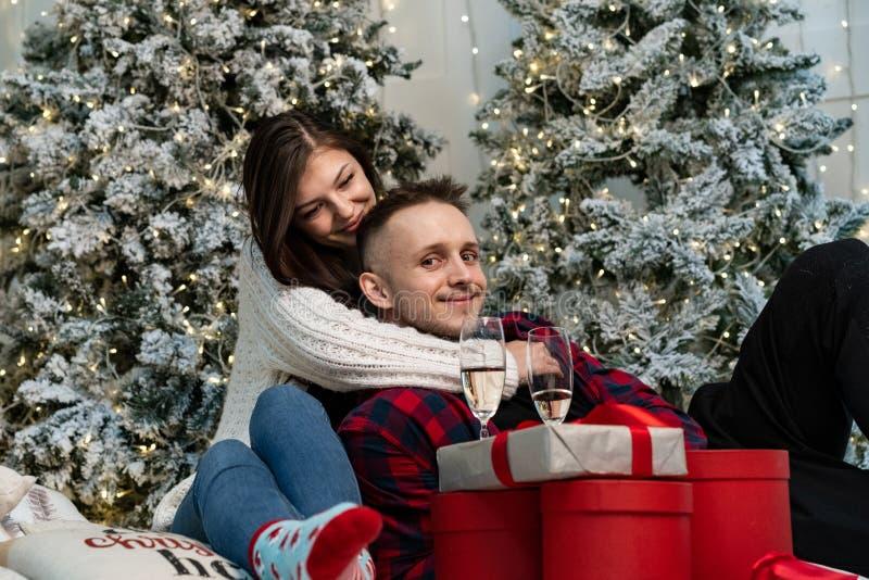 Pares románticos jovenes que celebran Año Nuevo cerca del árbol de navidad fotografía de archivo