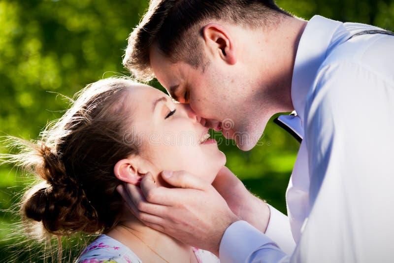 Pares románticos jovenes que se besan con amor en parque del verano imagenes de archivo