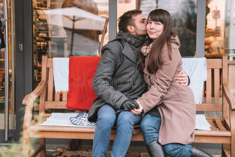 Pares románticos jovenes que se sientan en el banco y que admiran la naturaleza asombrosa imágenes de archivo libres de regalías