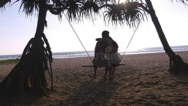 Pares románticos jovenes que se sientan junto en el oscilación en la playa y el abrazo tropicales del mar Pares en el amor que se imagen de archivo