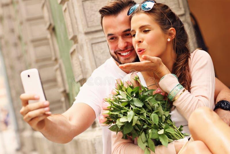 Pares románticos jovenes que toman el selfie en la ciudad imagen de archivo