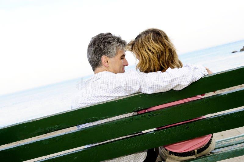 Pares románticos maduros en un banco imagenes de archivo