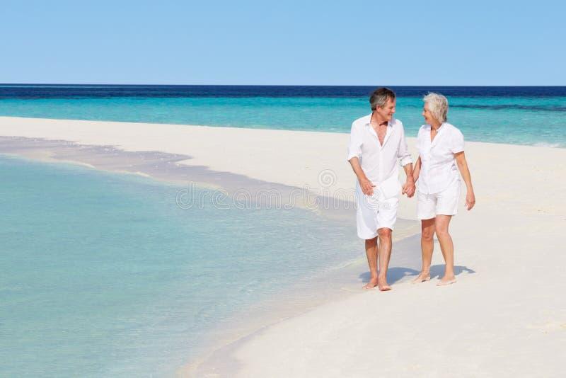 Pares románticos mayores que caminan en la playa tropical hermosa fotografía de archivo