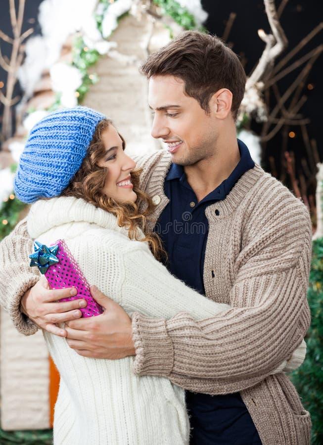 Pares románticos que abrazan en la tienda de la Navidad fotos de archivo