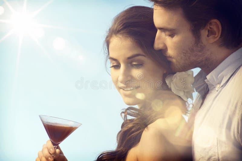 Pares románticos que beben en puesta del sol imagenes de archivo