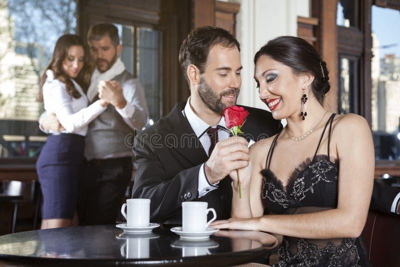 Pares románticos que detienen a Rose While Dancers Performing Tango fotografía de archivo