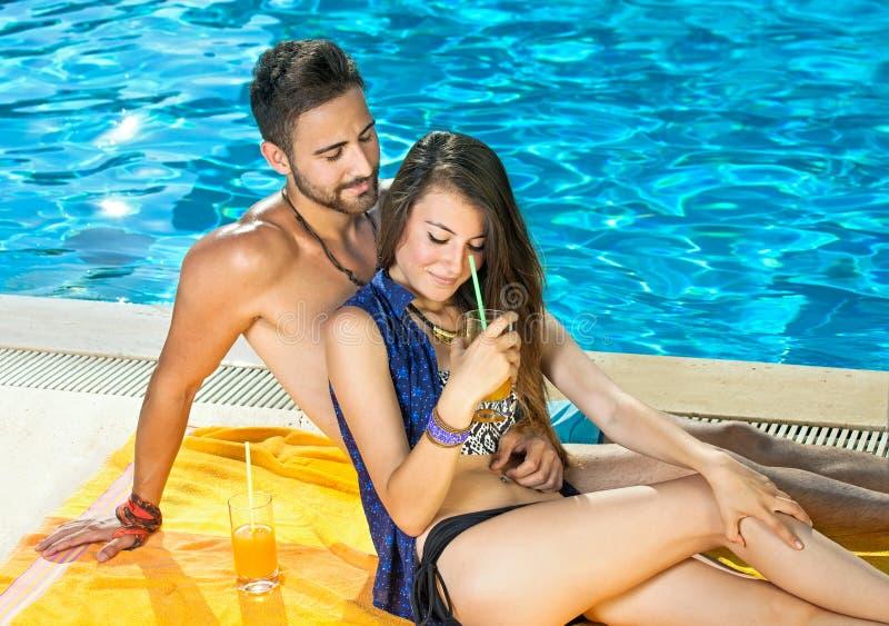 Pares románticos que gozan de los cócteles en la piscina foto de archivo