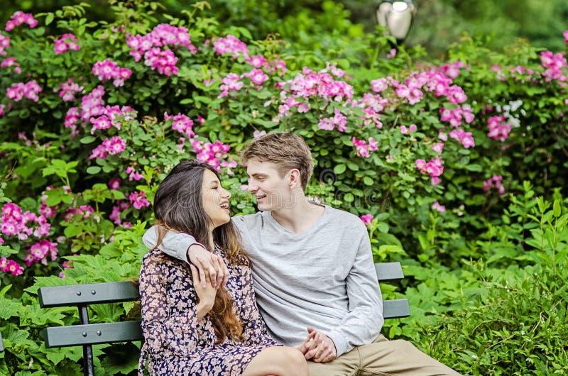 Pares románticos que hablan en banco en jardín fotografía de archivo libre de regalías