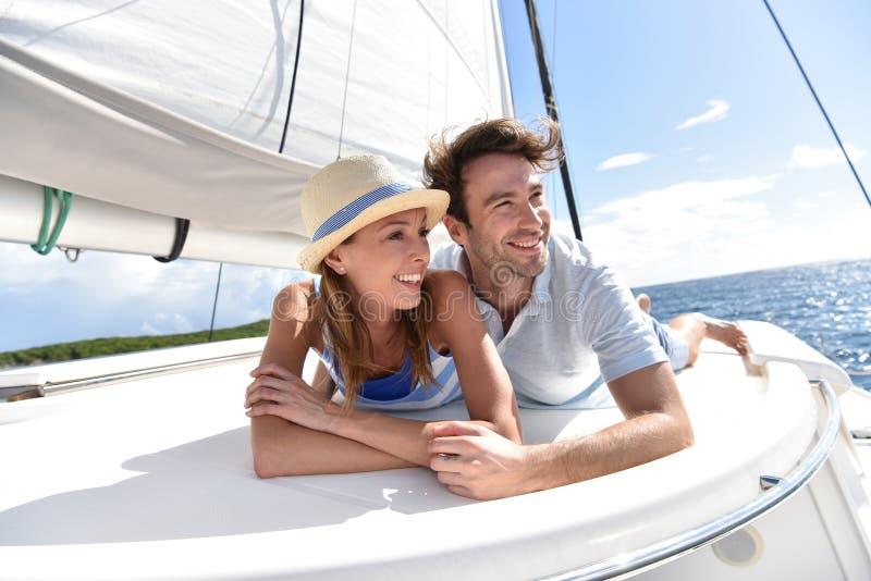 Pares románticos que mienten en la cubierta del barco de navegación fotografía de archivo