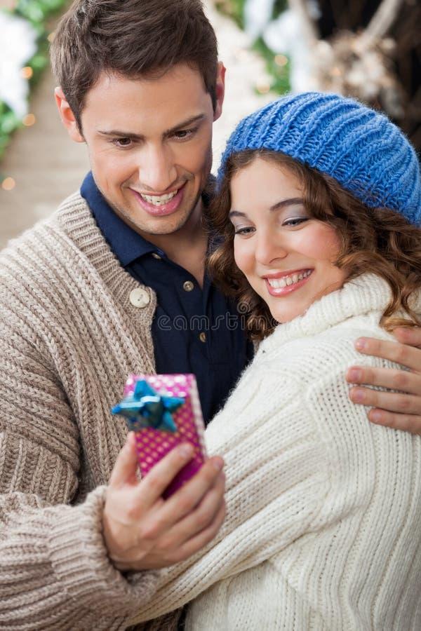 Pares románticos que miran la caja de regalo en tienda imagen de archivo