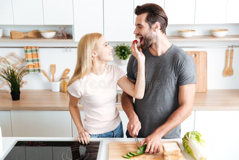 Pares románticos que preparan la cena en la cocina en casa foto de archivo