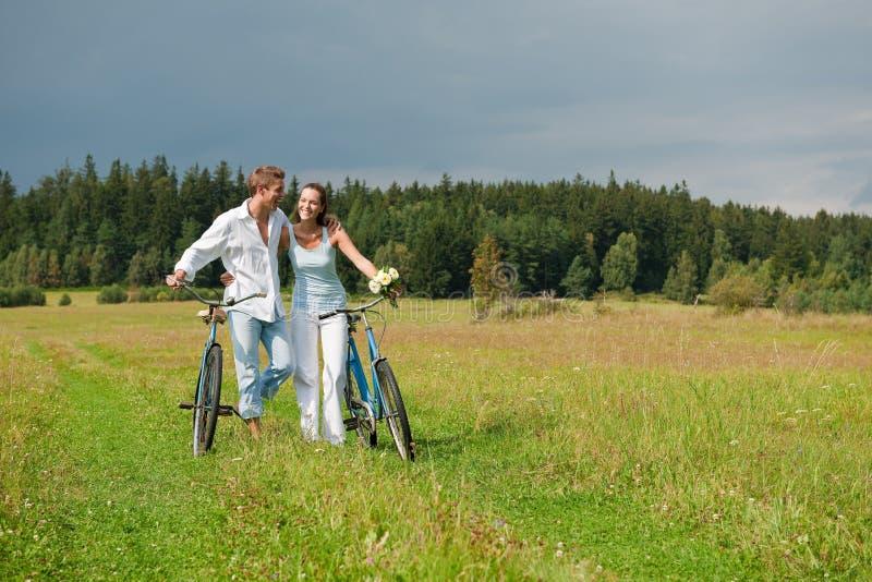 Pares románticos que recorren con la bici vieja en prado foto de archivo