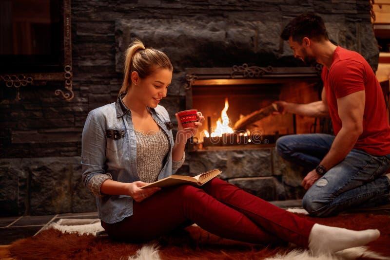 Pares románticos que relajan en casa delantero de la chimenea foto de archivo