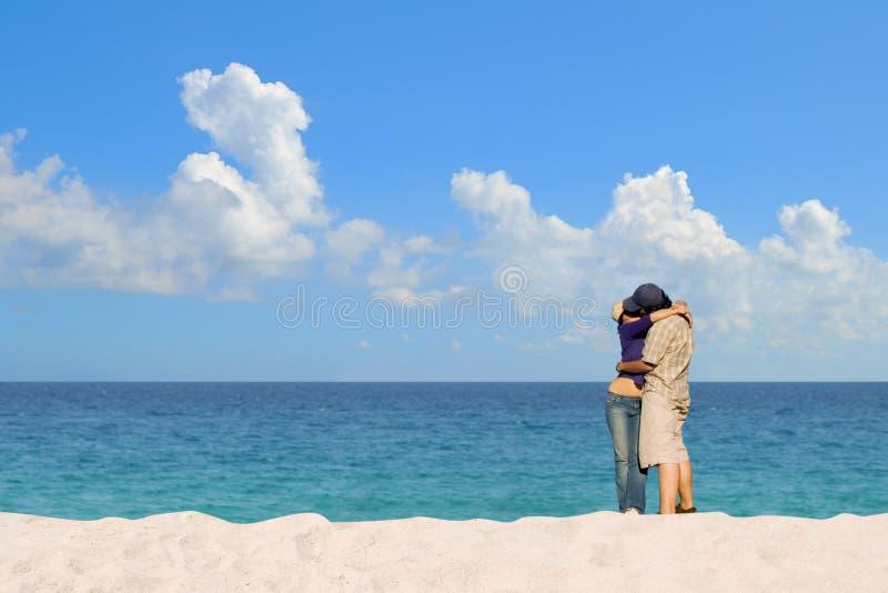 Pares románticos que se besan en la playa arenosa blanca foto de archivo libre de regalías