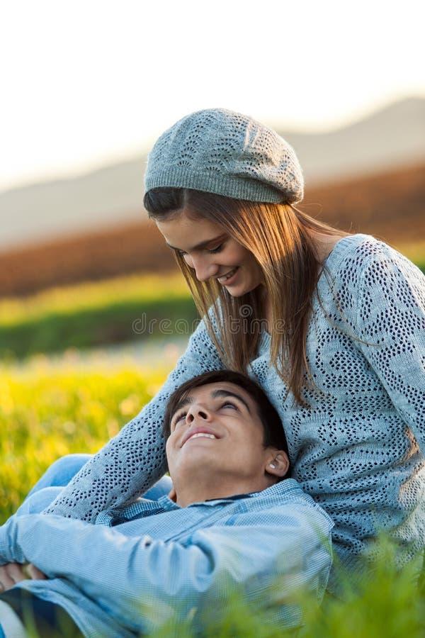 Pares románticos que se sientan en campo verde. fotos de archivo libres de regalías