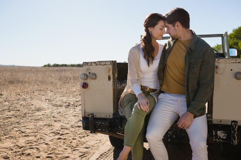 Pares románticos que se sientan en de vehículo de camino en el paisaje fotos de archivo