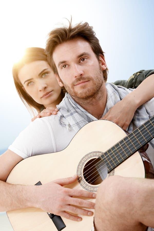 Pares románticos que se sientan en la playa que toca la guitarra fotos de archivo