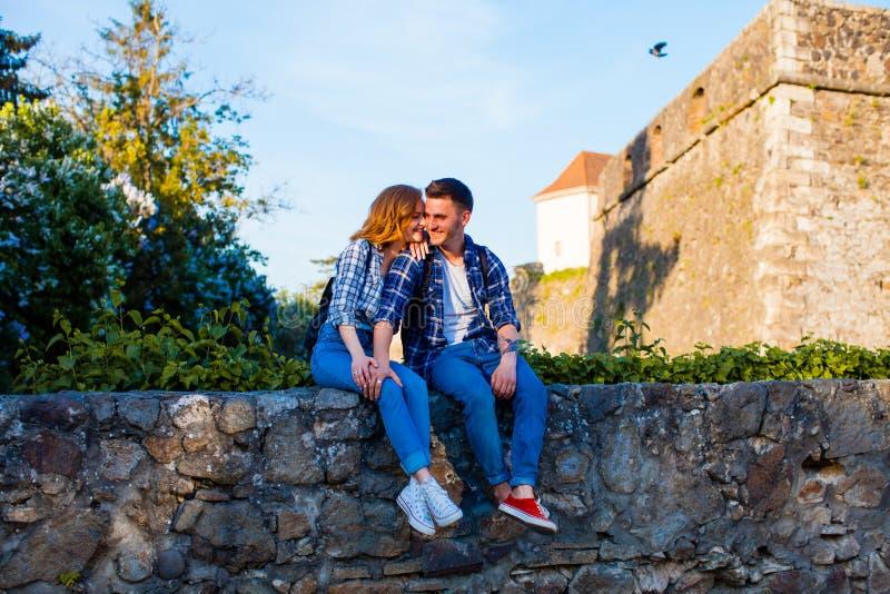 Pares románticos que se sientan en una pared cerca del castillo fotos de archivo libres de regalías