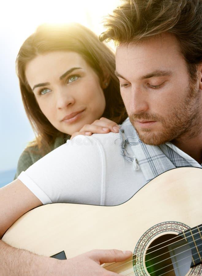 Pares románticos que se sientan jugando el ? al aire libre de la guitarra fotografía de archivo libre de regalías
