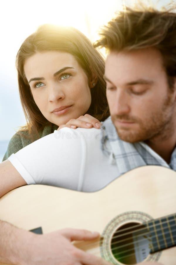 Pares románticos que se sientan jugando el ? al aire libre de la guitarra imagenes de archivo