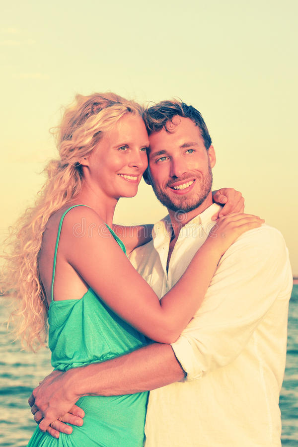 Pares románticos que sonríen y que abrazan en la playa foto de archivo