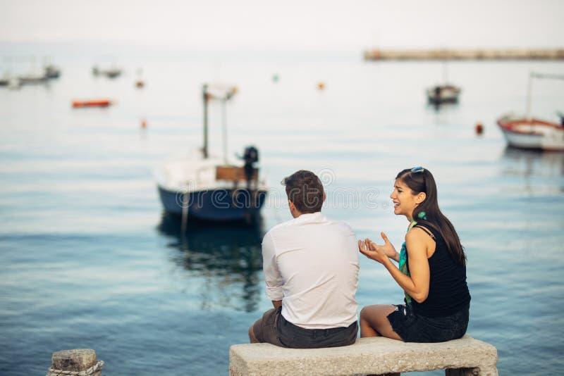 Pares románticos que tienen problemas de la relación Mujer que llora y que pide a un hombre Vida del pescador, empleo peligroso M foto de archivo