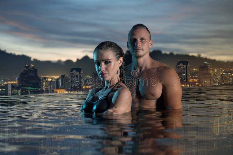 Pares românticos apenas na piscina da infinidade imagens de stock royalty free