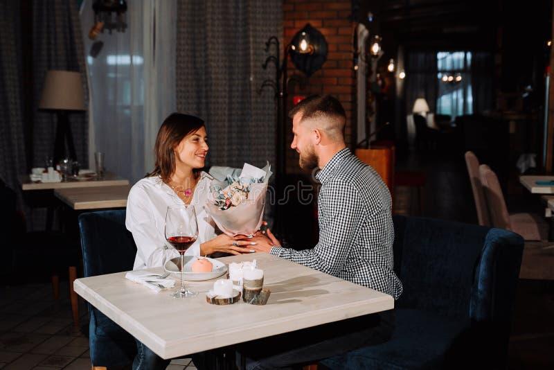 Pares românticos bonitos da surpresa no café O homem novo está apresentando flores à sua amado Sensação da felicidade imagens de stock