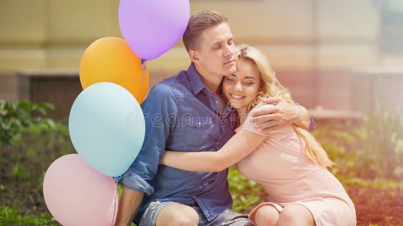Pares românticos bonitos que comemoram o aniversário, abraçando no banco no parque foto de stock