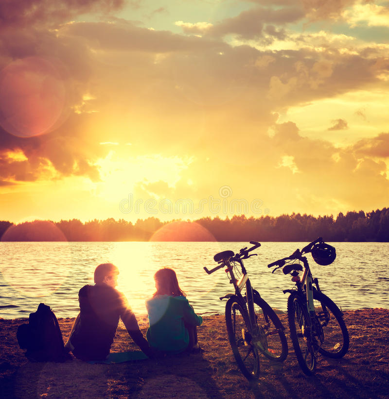 Pares românticos com as bicicletas pelo lago imagens de stock