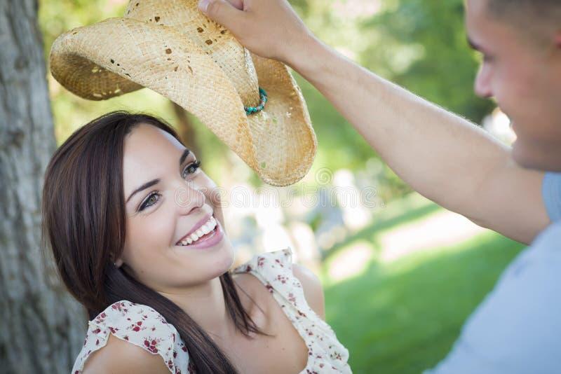 Pares românticos da raça misturada com vaqueiro Hat Flirting no parque fotografia de stock