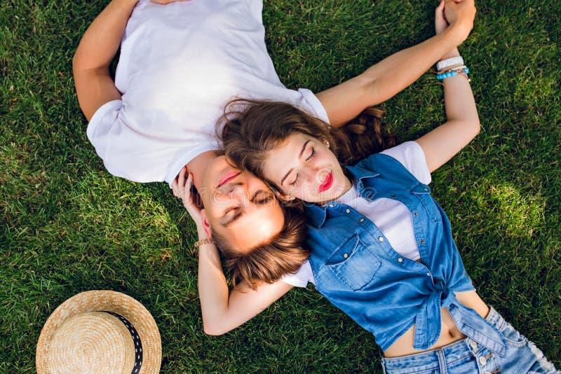 Pares românticos de jovens que encontram-se na grama no parque Colocam nos ombros de se e mantêm as mãos unidas fotografia de stock